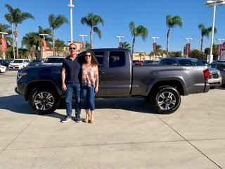 man and woman standing in front of gray truck